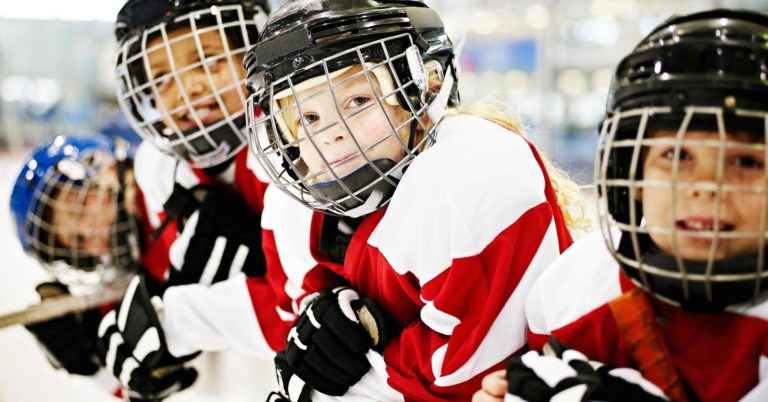 young hockey players looking over the bench