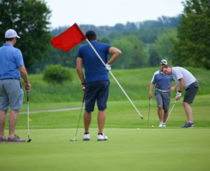 foursome lining up their puts on the green
