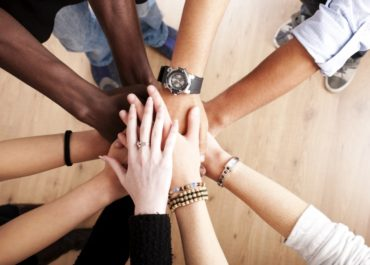 group of people with their hands together in a circle