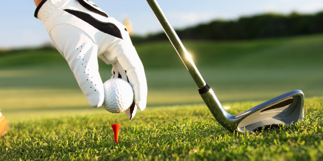 setting a golf ball on a tee
