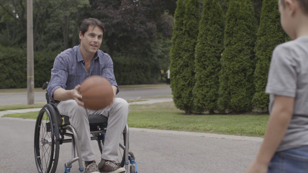 man in wheelchair playing ball with his young son